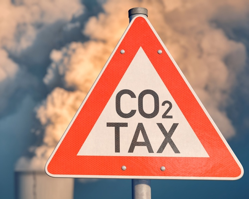 """Sign reads """"CO2 TAX"""" in front of smokestack"""